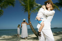 Women and child at beach. Two women and two children, male and female, dressed in white on a beach, caucasian/white Stock Photos