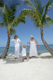 Women and child at beach. Two women holding the hands of a young girl at the beach with palm trees, caucasian/white Stock Photography