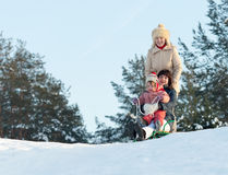 Women with child doing downhill on sleigh Royalty Free Stock Photography