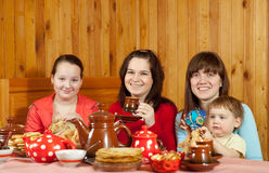 Women  with child drinks tea and eats pancakes Stock Images