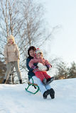 Women with child sliding on sleds Royalty Free Stock Image