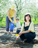 Women with child works at garden Royalty Free Stock Photos