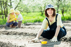 Women with child works at garden Stock Photos