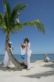 Women and children on beach. Two women with young boy and girl on a tropical beach with a palm tree, caucasian/white Royalty Free Stock Photos