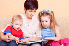 Women and children with book Stock Images