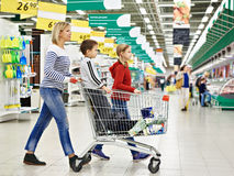 Women and children with cart shopping Stock Images
