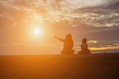Elder and sister watching the sunset stock photography