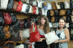 Women chooses leather bag at  shop Royalty Free Stock Image