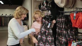 Women choosing dress during shopping at shop stock footage