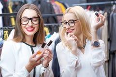Women choosing perfumes. Beautiful women choosing perfumes in the clothing store Royalty Free Stock Image
