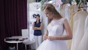 Women choosing wedding dress in shop. she is not completely. Girl chooses a wedding dress in a wedding salon stock video footage