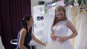 Women choosing wedding dress in shop. she is not completely. Girl chooses a wedding dress in a wedding salon stock video