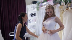 Women choosing wedding dress in shop. she is not completely stock video
