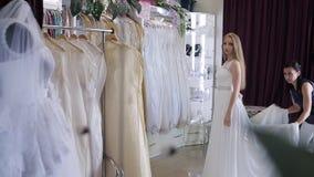 Women choosing wedding dress in shop. she is not completely. Girl chooses a wedding dress in a wedding salon stock footage