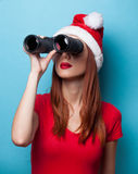 Women in christmas hat with binocular Royalty Free Stock Images