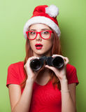 Women in christmas hat with binocular Royalty Free Stock Photos