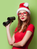 Women in christmas hat with binocular Stock Photography