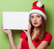Women in christmas hat with board Royalty Free Stock Photos