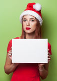 Women in christmas hat with board Royalty Free Stock Photography