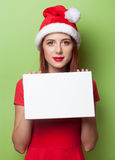 Women in christmas hat with board Royalty Free Stock Photo