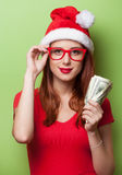 Women in christmas hat with money Royalty Free Stock Photos