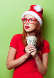 Women in christmas hat with money Royalty Free Stock Photography
