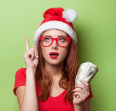 Women in christmas hat with money Stock Image