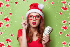 Women in christmas hat with money Stock Photo