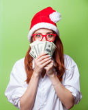 Women in christmas hat with money Stock Photos