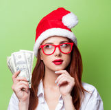 Women in christmas hat with money Royalty Free Stock Photo