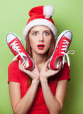 Women in christmas hat with red gumshoes Royalty Free Stock Image
