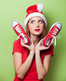 Women in christmas hat with red gumshoes Royalty Free Stock Photography