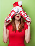 Women in christmas hat with red gumshoes Stock Images