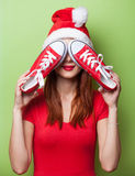 Women in christmas hat with red gumshoes Stock Photography
