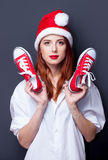 Women in christmas hat with red gumshoes Stock Photos