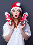 Women in christmas hat with red gumshoes Royalty Free Stock Images