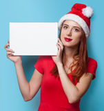 Women in christmas hat with white board Stock Images