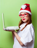 Women in christmas hat with white laptop computer Royalty Free Stock Image