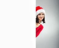 Women Christmas, looks out from behind the table Royalty Free Stock Photo