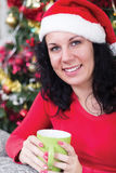 Women in Christmas night drinking hot tea, in the background Chr Royalty Free Stock Photography