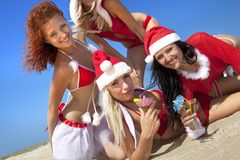 Women in christmas suit with martini on the beach Royalty Free Stock Photo