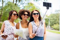 Women with city guide and map taking selfie royalty free stock photography