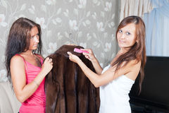 Women cleaning fur coat  with whisk. Two women cleaning fur coat  with whisk broom at home Royalty Free Stock Image