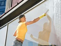 Women cleaning a window Stock Images
