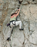 Women climber 3. Women whaching her footing while climbing cliff royalty free stock photography