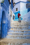 Women climbing a stair in the town of Chefchaouen in Morocco. Chefchaouen, Morocco - April 10, 2016: Women climbing a stair in the town of Chefchaouen in stock photo