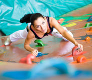 Women climbing on a wall. Woman climbing on a wall in an outdoor climbing center Stock Photography