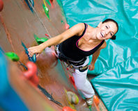 Women climbing on a wall Stock Images