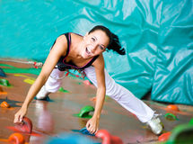 Women climbing on a wall. Woman climbing on a wall in an outdoor climbing center Stock Photo