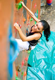 Women climbing on a wall. Woman climbing on a wall in an outdoor climbing center Royalty Free Stock Photos